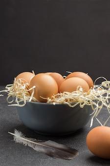 Braune eier in grauer keramikschale. vogelfeder und ein ei auf dem tisch. schwarze wand. speicherplatz kopieren