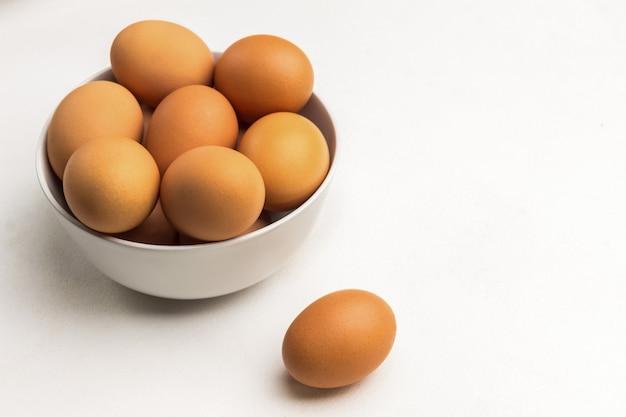 Braune eier in weißer keramikschale. ein ei auf dem tisch. speicherplatz kopieren. weiße oberfläche. draufsicht.