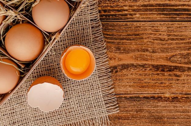 Braune eier und zerbrochenes ei mit eigelb auf holz
