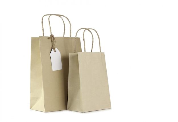 Braune einkaufstaschen und leeres etikett lokalisiert auf weiß