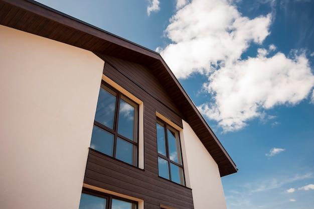 Braune fenster im skandinavischen stil in einem privaten häuschen gegen den himmel