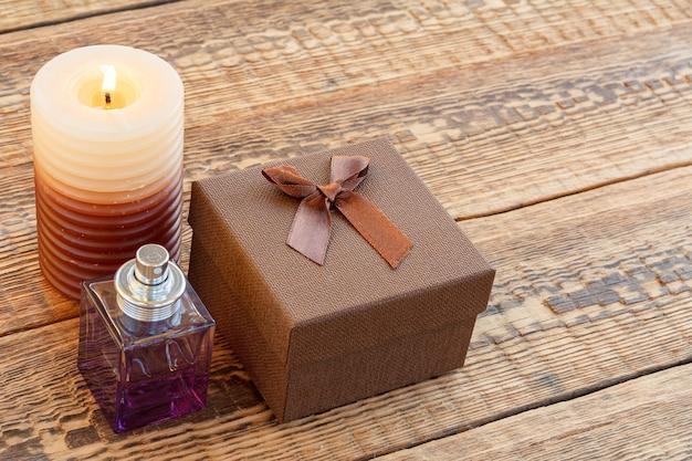 Braune geschenk- oder geschenkbox, ein parfüm und eine brennende kerze auf den alten holzbrettern. ansicht von oben. urlaubskonzept.
