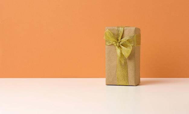 Braune geschenkbox auf weißem tisch, orangefarbenem hintergrund, überraschung und geschenk. platz kopieren