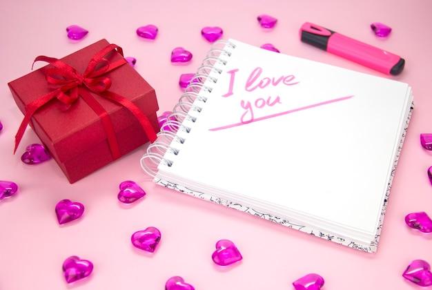 Braune geschenkbox der draufsicht und notizbuchpapier auf rosafarbenem pastellfarbhintergrund.
