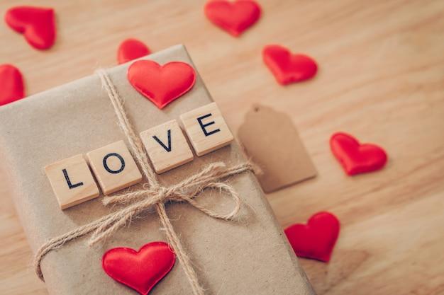 Braune geschenkbox der draufsicht und rotes herz auf hölzernem hintergrund für valentinstag mit kopienraum.