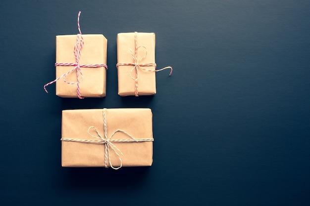 Braune geschenkbox im diy-stil auf dunklem hintergrund