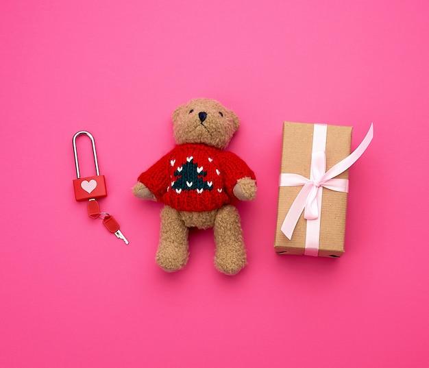 Braune geschenkbox und kleiner brauner teddybär auf einem rosa hintergrund,