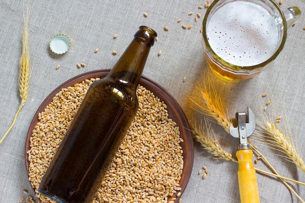 Braune glasflasche. keramikplatte mit weizen. becher bier und weizenähren