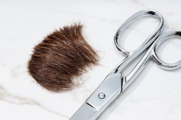 Braune haarsträhne und schere auf marmortisch. frisur oder haarschnitt-konzept. nahansicht