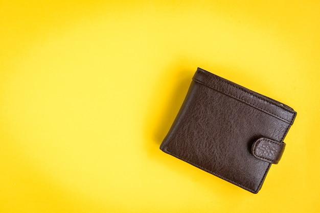 Braune herrenbrieftasche auf gelb.