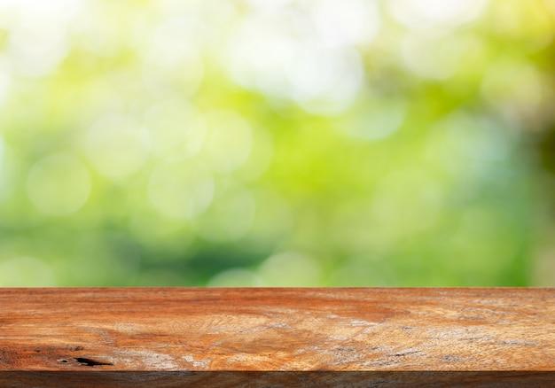 Braune hölzerne tischplatte auf einem grünen bokeh-unschärfehintergrund.