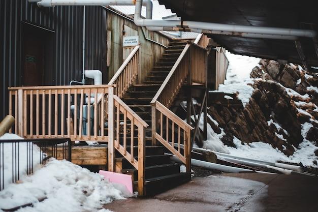 Braune holztreppe mit schnee bedeckt