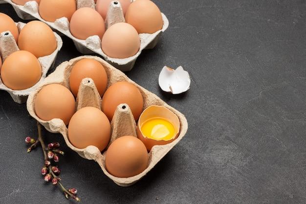 Braune hühnereier im kartonbehälter. ein zerbrochenes ei im behälter. eierschale auf dem tisch. speicherplatz kopieren. draufsicht.