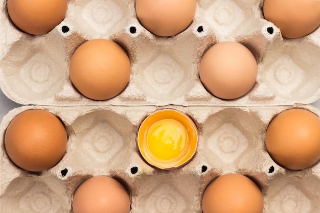 Braune hühnereier im kartonbehälter. ein zerbrochenes ei im behälter. flach liegen
