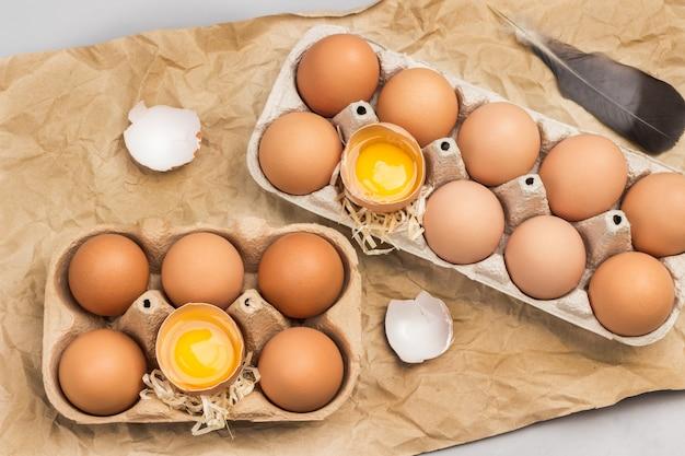 Braune hühnereier im kartonbehälter. gebrochene eier im behälter. eierschale auf dem tisch.