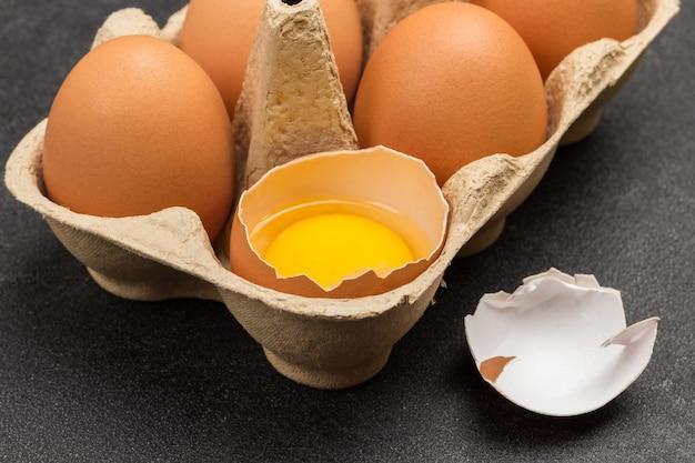 Braune hühnereier im kartonbehälter. gebrochenes ei im behälter. muscheln auf dem tisch.