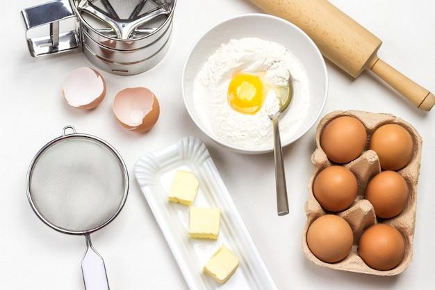 Braune hühnereier im kartonbehälter, mehl, zerbrochenes ei und löffel in schüssel auf weißem hintergrund