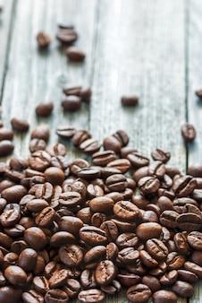 Braune kaffeebohnen auf grauer holzoberfläche vertikaler schuss