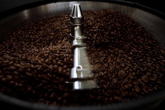 Braune kaffeebohnen in der röstmaschine, nahaufnahme von sportfokus und langzeitbelichtung