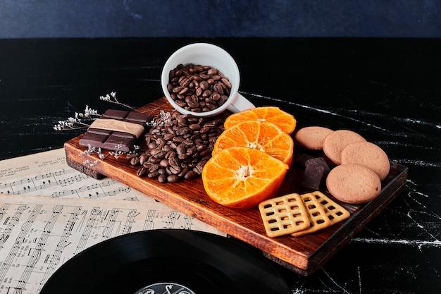 Braune kaffeebohnen mit orangenscheiben und keksen