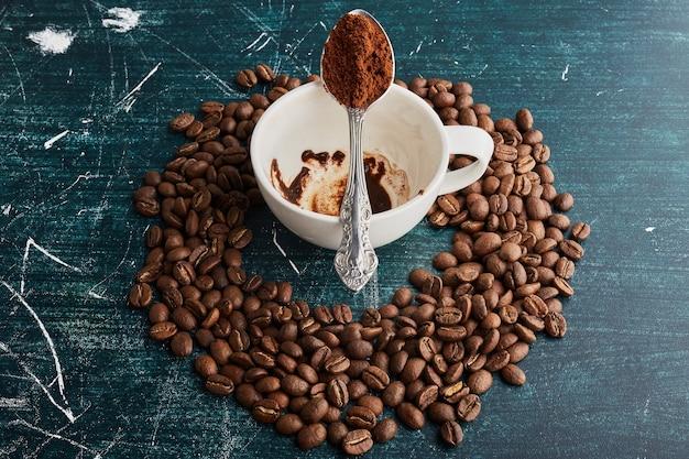 Braune kaffeebohnen und eine schmutzige kaffeetasse in der mitte.