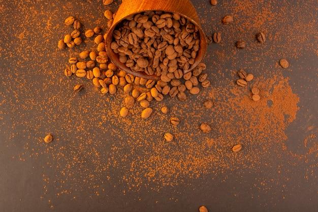 Braune kaffeesamen der draufsicht innerhalb der braunen platte auf dem dunklen körnchengranulat des braunen hintergrundkaffeesamens