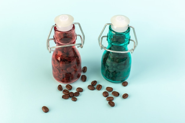 Braune kaffeesamen einer vorderansicht in farbigen gläsern auf der blauen oberfläche