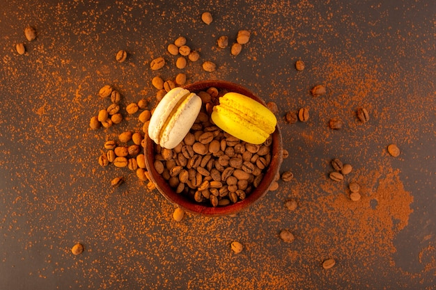 Braune kaffeesamen von oben in der braunen platte mit französischen macarons auf dem braunen tisch