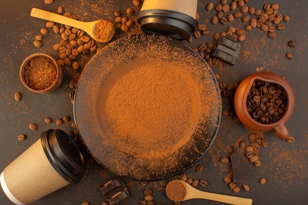 Braune kaffeesamen von oben mit schwarzen kaffeetassen mit schokoriegeln