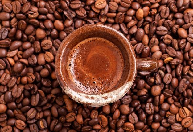 Braune kaffeetasse auf kaffeebohnen hintergrund