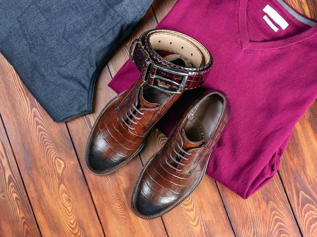 Braune krokodillederschuhe und ein hosengürtel neben jeans und einem pullover auf einem hölzernen hintergrund