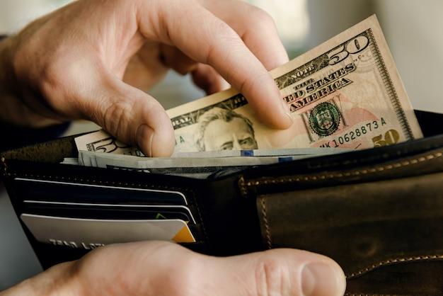 Braune lederbrieftasche mit dollars in den händen