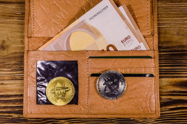 Braune ledergeldbörse mit fünfzig euro-banknoten und bitcoins auf dem hölzernen hintergrund. ansicht von oben