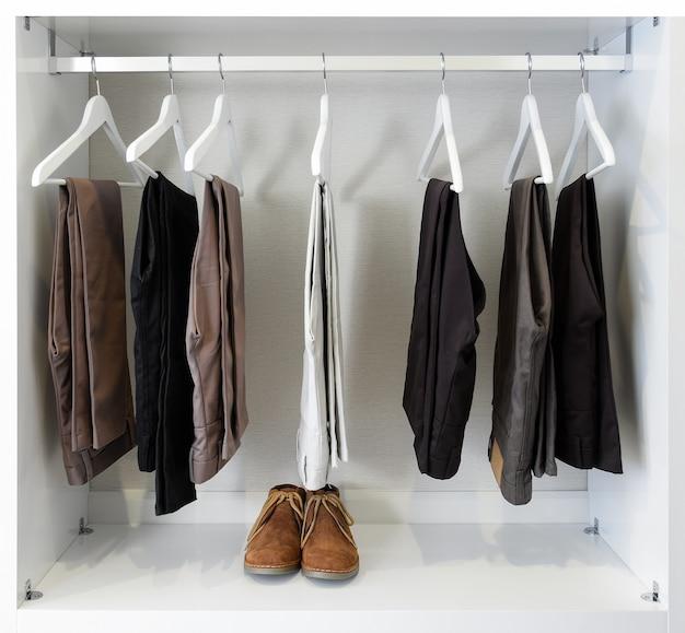 Braune lederschuhe und eine reihe von schwarzen hosen hängen in der garderobe