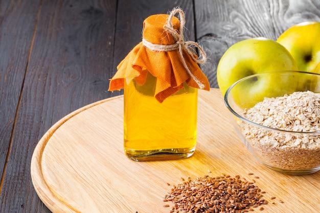 Braune leinsamen auf löffel und leinsamenöl im glaskrug auf holztisch. flachsöl ist reich an omega-3-fettsäuren.