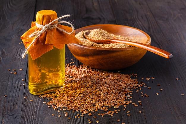 Braune leinsamen in löffel und leinsamenöl in glasflasche auf weißem holz. flachsöl ist reich an omega-3-fettsäuren