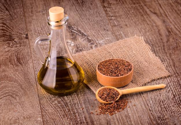 Braune leinsamen und leinsamenöl auf einer holzoberfläche