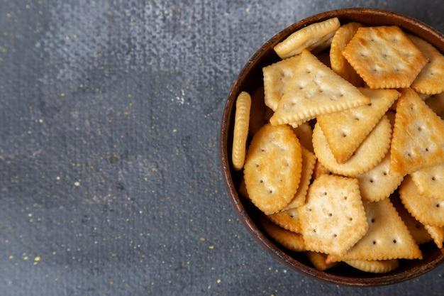 Braune metallplatte der oberen nahansicht mit gesalzenen crackern innen auf dem knackigen crackersnackfoto des grauen hintergrunds