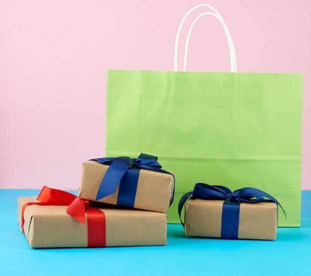 Braune papierbox mit einem geschenk und bunten papiertüten zum einkaufen
