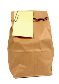 Braune papiertüte mit gelbem post-it haftnotiz stil