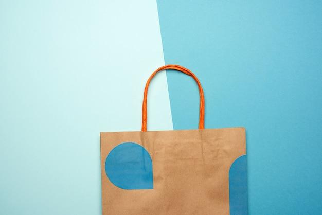 Braune papiertüte mit griffen zum einkaufen auf einem blauen hintergrund, flache lage