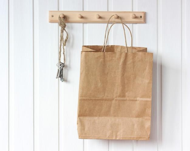 Braune papiertüte und schlüssel auf einem kleiderbügel. konzept der natürlichen verpackung.