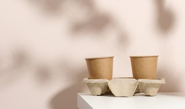 Braune pappbecher für kaffee und tee, beigefarbener hintergrund. umweltfreundliches geschirr, null abfall