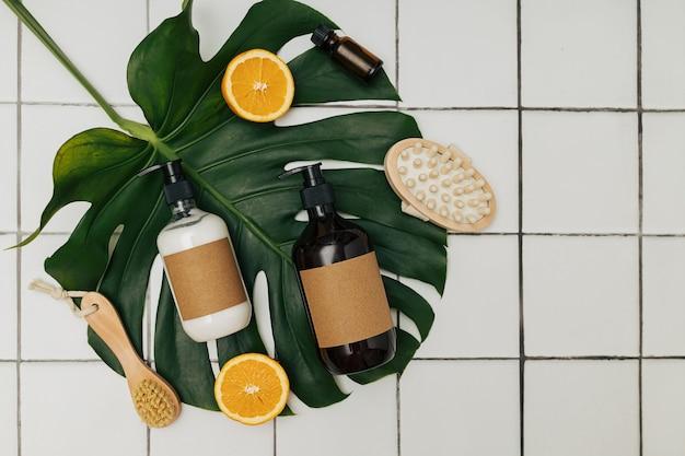 Braune plastik- und glasflaschen mit umweltfreundlicher bio-kosmetik, grünem monstera-blatt und geschnittenen orangen von oben. beauty-minimalismus-konzept. naturkosmetik-inhaltsstoffe für die hautpflege.