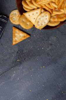Braune platte der draufsicht mit crackern auf dem knusper-snackfoto des grauen schreibtischs