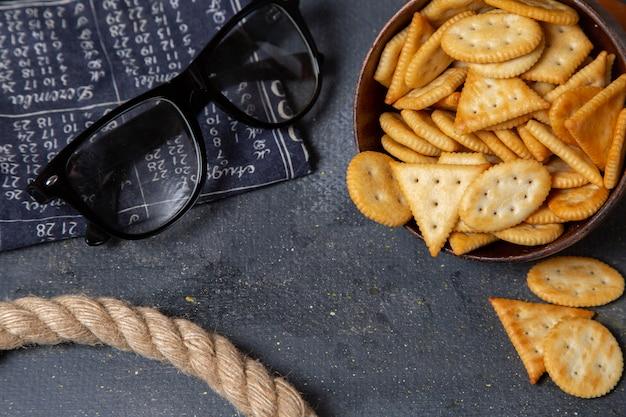 Braune platte der draufsicht mit crackern und seilen auf dem foto-snack des knusprigen crackers des grauen hintergrunds