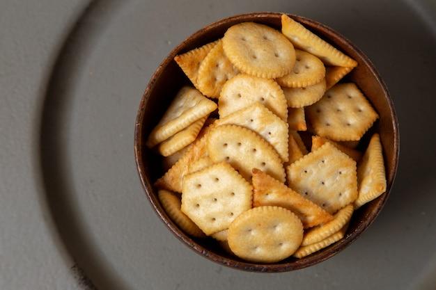 Braune platte der oberen nahansicht voller gesalzener chips auf dem knusper-snackfoto des grauen hintergrunds