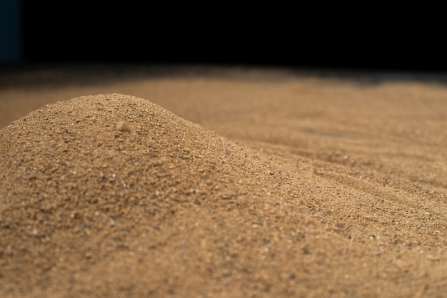 Braune sandoberfläche auf schwarzer wand