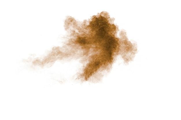 Braune staubexplosionswolke. braune partikel spritzen auf weißem hintergrund.