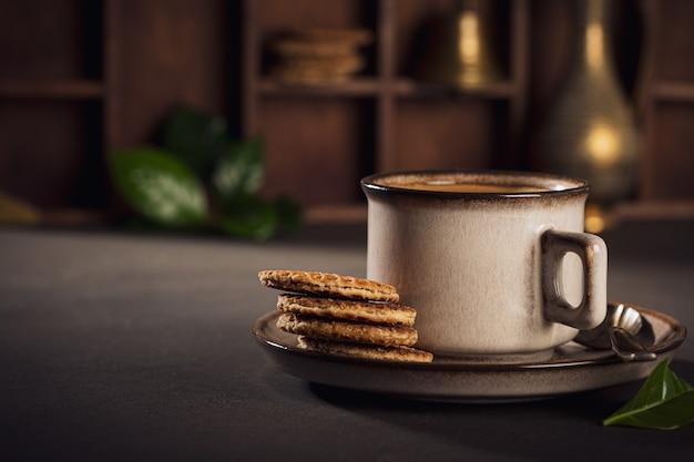 Braune tasse kaffee und niederländische traditionelle stroopwafels. lebensmitteloberfläche mit kopierraum